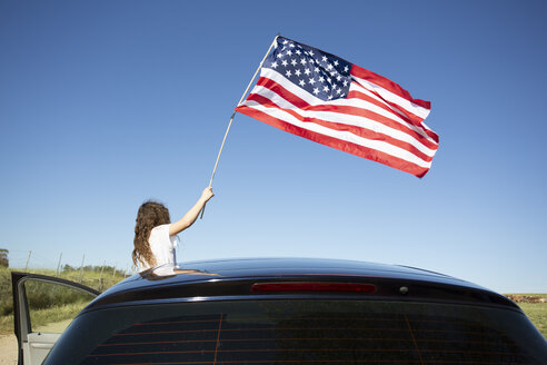 Girl holding American flag out of a car under blue sky - ERRF00208