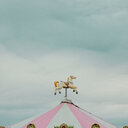 Low angle view of a ornament of a horse on top of a tent under a cloudy sky - INGF08454
