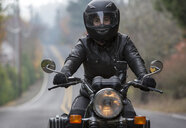 Female biker wearing crash helmet while riding motorcycle on road - CAVF57471
