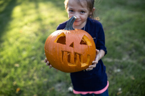 Portrait of girl holding jack o lantern while standing on field in yard - CAVF57498