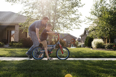 Father assisting son in riding bicycle on road against sky - CAVF57534