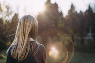 Rear view of girl standing at park during sunny day - CAVF57540