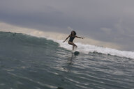 Woman surfing on sea against cloudy sky - CAVF57543