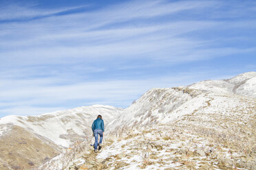 Rear view of woman climbing on mountain against cloudy sky during winter - CAVF57561