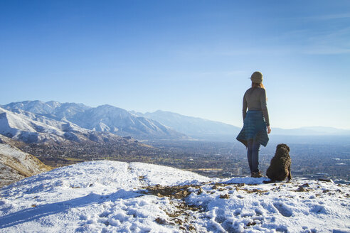 Rear view of woman with dog standing on mountain against sky during winter - CAVF57564
