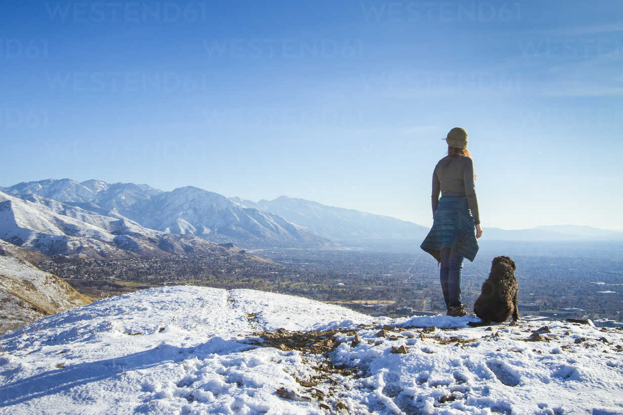 Rear view of woman with dog standing on mountain against sky during winter - CAVF57564 - Cavan Images/Westend61