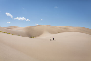 High angle view of hikers walking on desert at Great Sand Dunes National Park during sunny day - CAVF57570