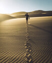 Rear view of carefree woman walking on sand at Great Sand Dunes National Park during sunset - CAVF57576