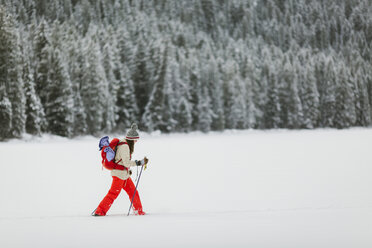 Side view of woman hiking on snow covered field - CAVF57579
