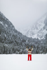 Woman with hiking poles standing on snow covered field - CAVF57582