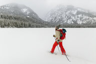 Side view of woman with backpack hiking on snow covered landscape - CAVF57585
