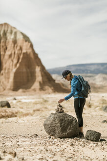 Side view of female hiker stacking rocks while standing at desert - CAVF57591