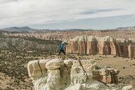 Full length of female hiker jumping on rock formation at desert - CAVF57597