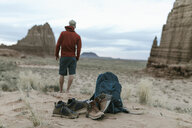 Full length of hiker looking at view with shoes ad backpack in foreground on desert - CAVF57600