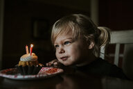 Cute girl looking at her birthday cake on table - CAVF57615