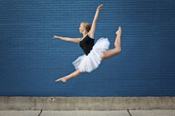 Ballerina dancing by brick wall - CAVF57618