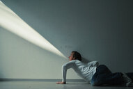 Side view of a man playing with light on a wall - INGF08469