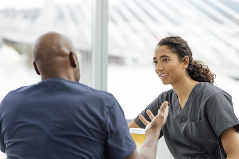 Mature male nurse talking with female colleague in hospital - TGBF01804