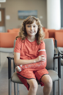 Portrait of girl with plastered arm sitting on chair in hospital - TGBF01831