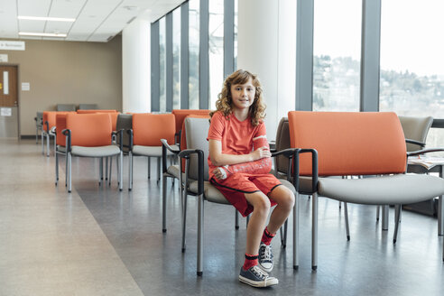 Full length portrait of girl with plastered arm sitting on chair in hospital - TGBF01855