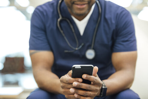 Midsection of mature male nurse using mobile phone in hospital - TGBF01858