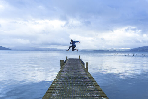 Young man jumping on pier over lake against sky - TGBF01879