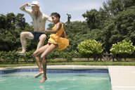 Happy couple jumping into swimming pool against sky at tourist resort - CAVF57644