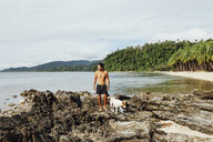 Shirtless hiker with dog standing on rocks against sky at beach - CAVF57659