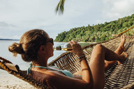 Young woman drinking alcohol while resting in hammock at beach - CAVF57668
