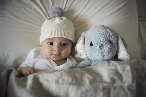 High angle view of baby boy with teddy bear lying on bed at home - CAVF57692