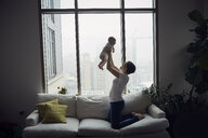 Side view of happy mother lifting son while kneeling on sofa by window at home - CAVF57698