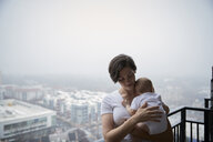 Mother carrying son while standing in balcony during foggy weather - CAVF57704