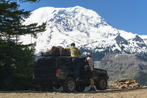 Hiker adjusting luggage on off-road vehicle by friend against snowcapped mountains - CAVF57725