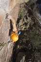 High angle view of confident female hiker climbing mountain - CAVF57728
