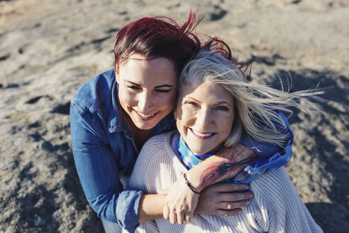 High angle portrait of cheerful mother with daughter on rocks - CAVF57734