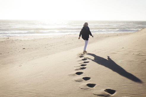 Rear view of senior woman walking on sand at beach against clear sky during sunny day - CAVF57737