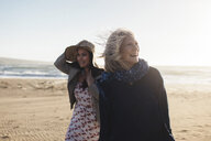 Happy mother and daughter at beach against clear sky during sunny day - CAVF57740