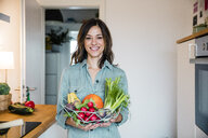 Woman standing in kitchen, holding basket full of fresh fruit and vegetables - MOEF01711
