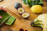 Person preparing healthy fruit, slicing paaion fruits and aloe vera - MOEF01720