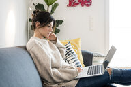 Woman sitting on her couch, surfing the net, using laptop - MOEF01735