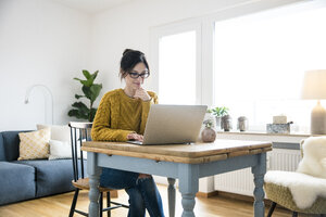 Woman sitting at table, using laptop - MOEF01744