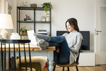 Woman sitting at table with feet up, using laptop - MOEF01747
