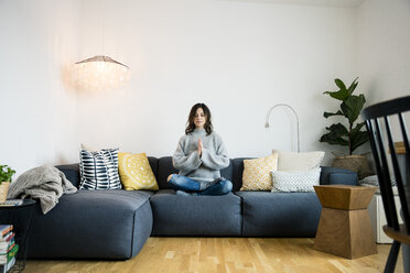 Mature woman sitting cross-legged on couch with eyes closed, meditating at home - MOEF01750