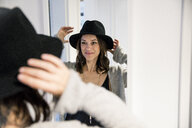 Mature woman standing in front of mirror , putting on a hat - MOEF01756
