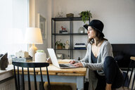 mature woman with hat, sitting at home, using laptop - MOEF01759