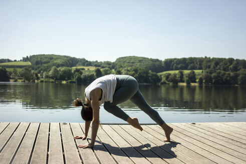 Mature woman practicing yoga in summer on a jetty at a lake - MOEF01762