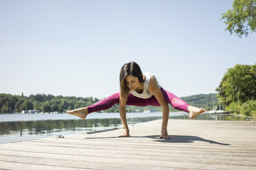 Mature woman practicing yoga in summer on a jetty at a lake - MOEF01765