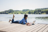 Mature woman working at a lake, using laptop on a jetty - MOEF01771