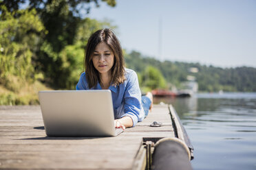 Mature woman working at a lake, using laptop on a jetty - MOEF01774