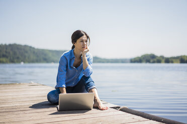 Mature woman working at a lake, using laptop on a jetty - MOEF01777
